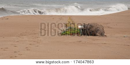 Lobster traps on shore with crashing waves in background