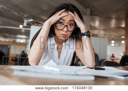 Upset Asian business woman in suit and eyeglasses which sitting by the table in office and looking at camera