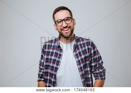 Bearded man in shirt and eyeglasses which looking at camera. Isolated gray background
