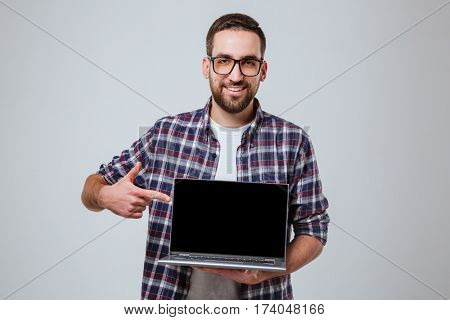 Bearded man in eyeglasses which showing blank laptop screen and pointing at him while looking at camera. Isolated gray background
