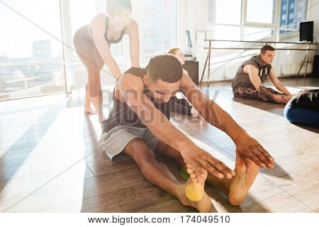 Barefoot african young man doing stretching yoga exercises with instructor in studio