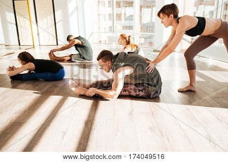 Group of people stretching and practicing yoga with trainer in studio