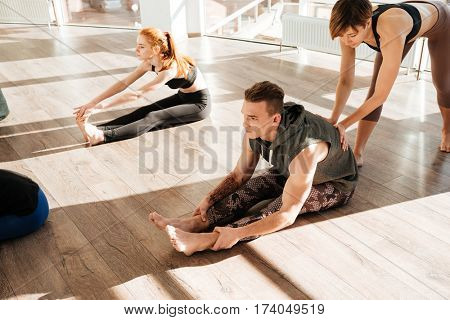 Group of people doing stretching yoga exercises with instructor in studio