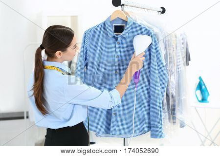 Woman with steamer cleaning clothes in dry-cleaning salon