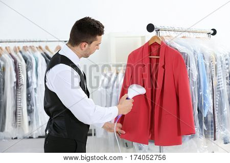 Man with steamer cleaning clothes in dry-cleaning salon
