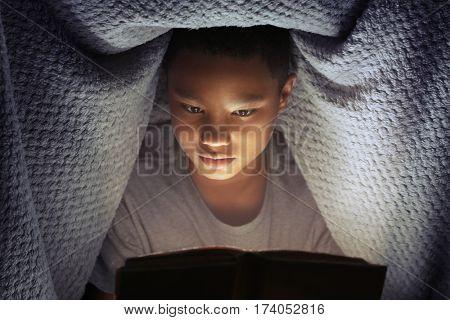 Cute boy reading book at night
