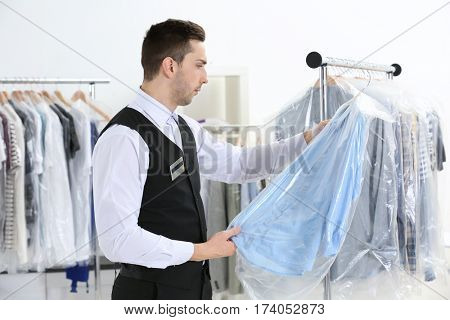 Young man working in dry-cleaning salon