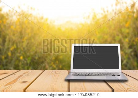 Laptop with blank screen on wooden table with absract yellow flower and flare light background can used for display or montage your products