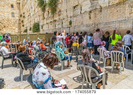JERUSALEM, ISRAEL - MAY 23, 2016: Women praying and making their wishes at the Western Wall, Wailing Wall or Kotel witch is located in the Old City at the foot of the western side of the Temple Mount.
