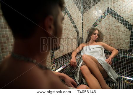 Gorgeous longhaired young blonde wrapped in white towel posing in hamam his young sexy lover looking at her