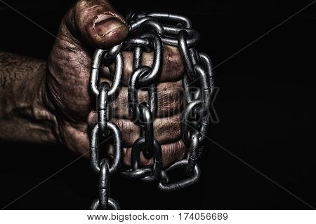 Hand with CHAINchain in handthe chain wound on the handdirty handsblack background