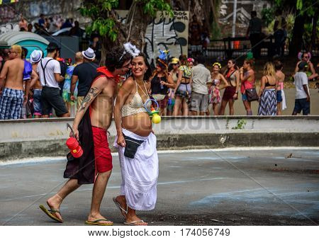 RIO DE JANEIRO, BRAZIL - FEBRUARY 28, 2017: Happy costume husband with hammer and sickle and his pregnant wife with enormous plastic pacifier having fun at Carnaval 2017