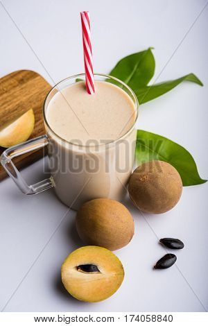 tasty and healthy Chikoo or chiku Milkshake Recipe (Sapota Milkshake) | Chikku Milkshake with chopped pieces over wooden chopping board and green leaves