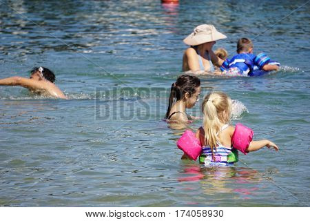 HARBOR SPRINGS, MICHIGAN / UNITED STATES - AUGUST 3, 2016: Children enjoy swimming in the water at the Zorn Park Public Beach near downtown Harbor Springs.