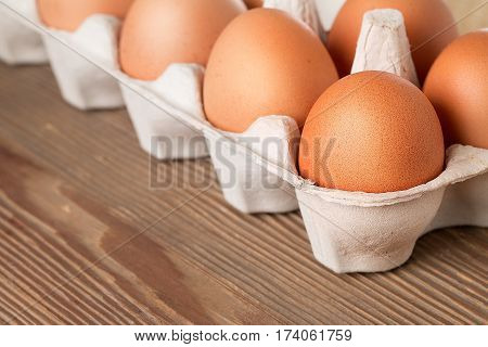 Eggs in box on a wooden table.  brown eggs in a carton package