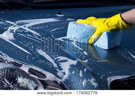 turquoise car is washing in soap suds