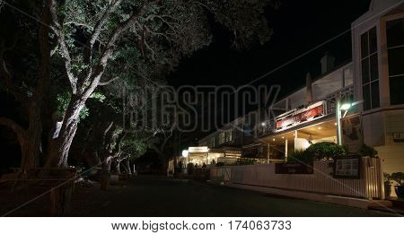 Russell , New Zealand - February 8, 2017; tourism town in Bay of Islands at night colonial buildings along the Strand with lights shining up into pohutukawa trees on harbor side of street New Zealand.