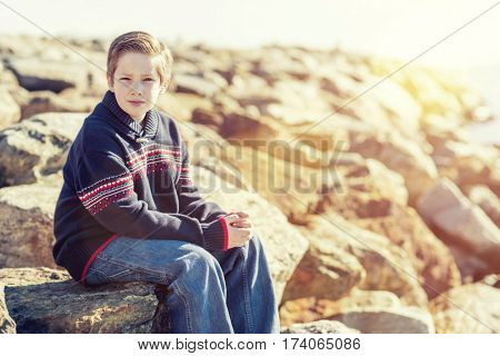Thoughtful young boy sitting on rocks