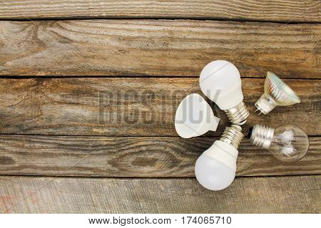 Different light bulbs on the old wooden background. Top view.