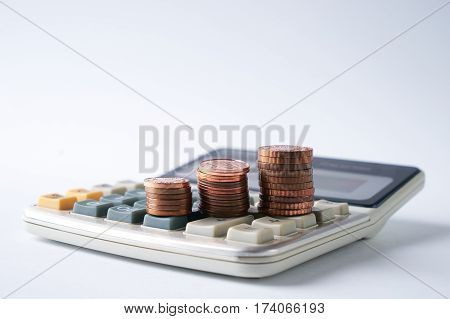 Close-up of stacked gold coins on calculator on isolated white background with copy spase concept of accounts.