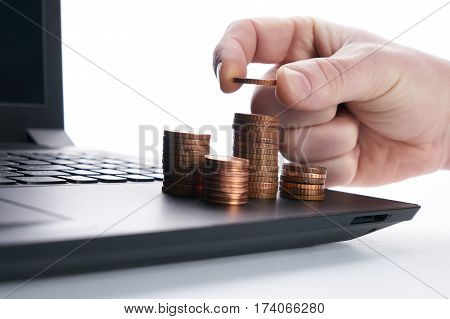 Banking financial concept. Stack of golden coins on laptop keyboard.Businessman hand putting gold coin on stack of coins.