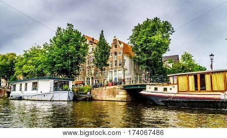 Historic houses dating back to the Middle Ages along the canals seen from a boat in canals of Amsterdam