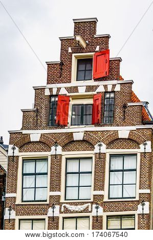 Step Gable with Red Shutters in front of the upper windows of a Historic House along the Canals in Amsterdam, the Netherlands