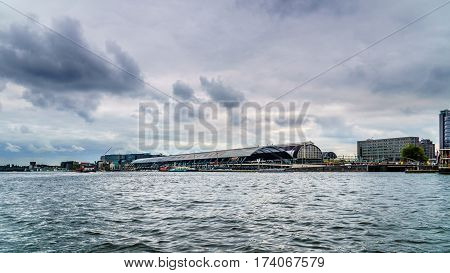 View of Central Train Station along the Harbor named Het IJ in Amsterdam, the Netherlands