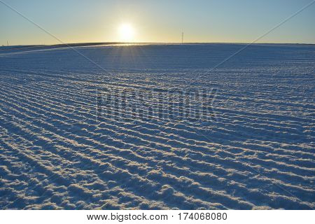 snowy frosty winter time agriculture farm field and morning sunlight