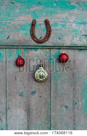 happy lucky Christmas and New year. Old rusty horseshoe Christmas toys and vintage clock on wooden door