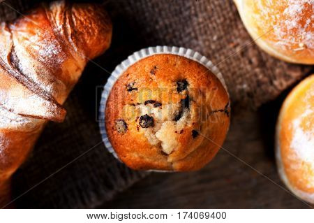 Delicious Chocolate muffins croissants and dark chocolate pieces on wooden table - Food background bakery concept close up image