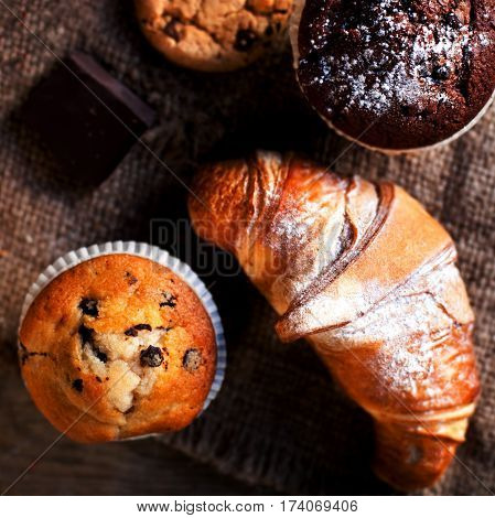 Delicious Chocolate cupcakes croissants and dark chocolate pieces on wooden table - Food background bakery concept close up image