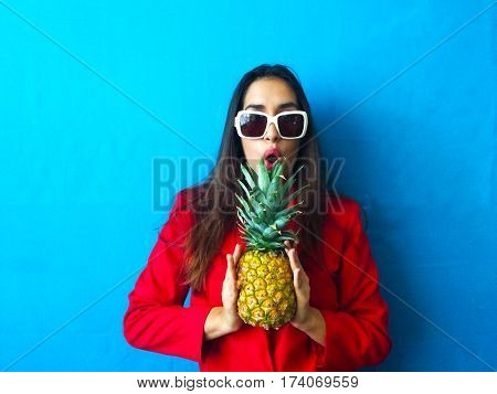 Fashion sexy retro vintage and natural surprised model in white sunglasses with pineapple fruit in her hand with long brunette hair and red clothes in bright vibrant blue background