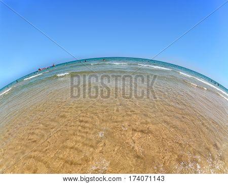 Wide angle sandy beach on the Mediterranean Sea, blue sky and sea, the fish-eye