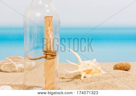Message in bottle on the tropical sea with seashell e stones