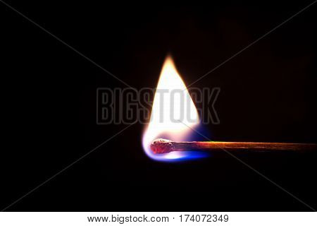 Burning match on a black background, light