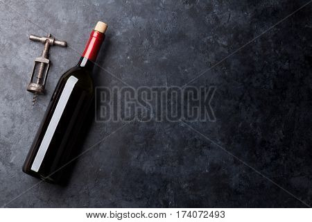 Red wine bottle and corkscrew on stone background. Top view with copy space