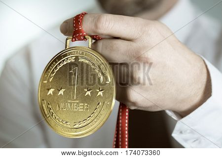 Man holding a golden award where it is written number one. Concept of business excellence. Composite image between a hand photography and a 3D medal.