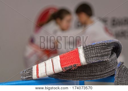 Jiu-jitsu belt in front with athletes blurred on back