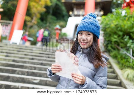 Woman holding famous cracker in Kamakura city