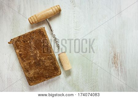 A vintage corkscrew, a cork, and an old notebook for wine tasting notes, shot from above on a wooden background texture with a place for text
