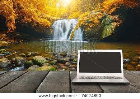 Laptop with blank screen on wooden table with waterfall in forest background can used for display or montage your products