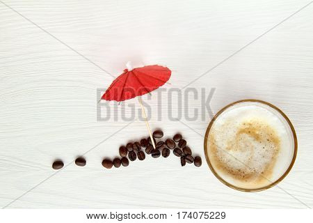 frothy latte beside red umbrella and beans top view / hot drink to relax