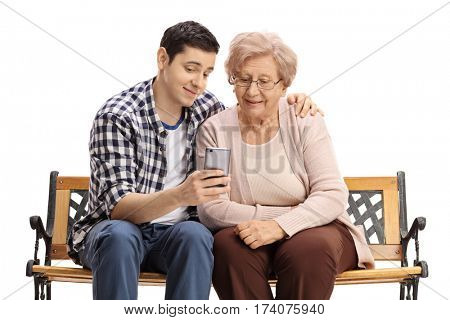 Young man sitting on a bench with a mature woman and showing her something on a phone isolated on white background