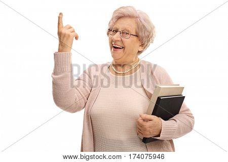 Joyful senior pointing up with her finger isolated on white background