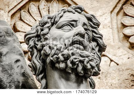 Stone sculpture showing head of man with curly hair.
