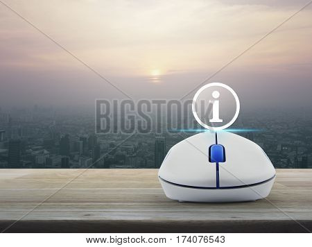Information sign icon with wireless computer mouse on wooden table over modern city tower at sunset vintage style Customer support concept