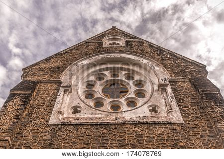 Facade of the catholic church with a cloudy sky background closeup.