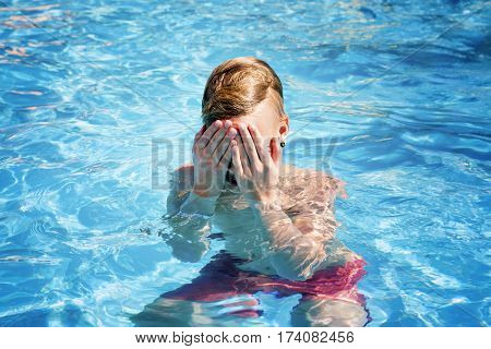 Teenager hides the face in hands in the pool. Concept of wound and trauma.