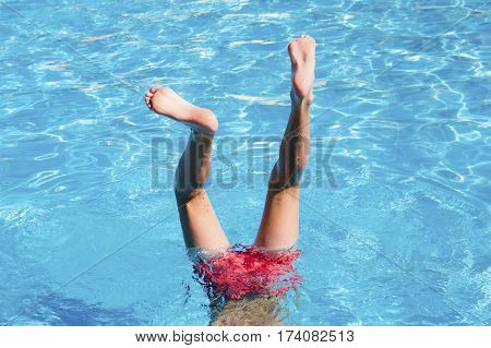 Teenager has fun in waterpark. Feet in the pool close up